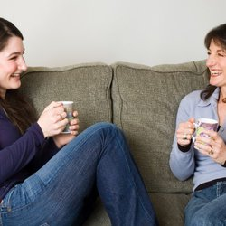 2 womens laughing sat on sofa.jpg